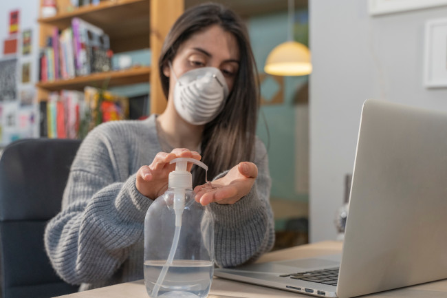 Woman at desk wearing mask and using hand sanitizer - Shutterstock