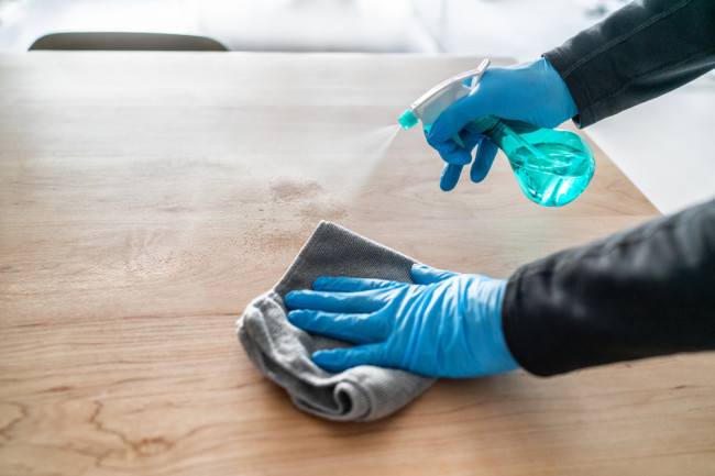 Two hands in latex gloves clean a tabletop with a spray bottle and rag - Shutterstock
