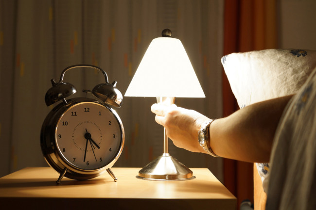 Arm reaches out of bed and turns on a light in the middle of the night - Shutterstock