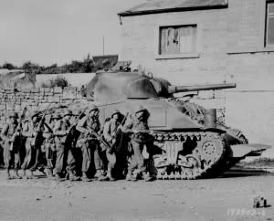 Troops of the 60th Infantry Regiment advance into a Belgian town under the protection of a Sherman tank. Credit: Sgt. William Spangle, September 9, 1944 / Courtesy U.S. National Archives