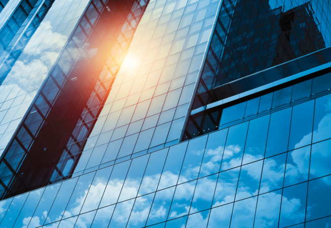 Skyscraper or modern building in the city with cloud and sunlight - shutterstock