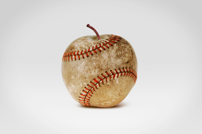 An old shabby baseball with red stitches in the form of an apple isolated on white background - shutterstock 1008879742