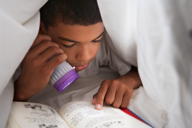 Boy Child Reading in Bed Flashlight - Shutterstock
