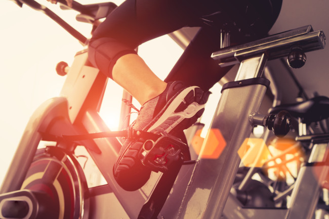 Person riding exercise bike, Fitness Metabolism - Shutterstock