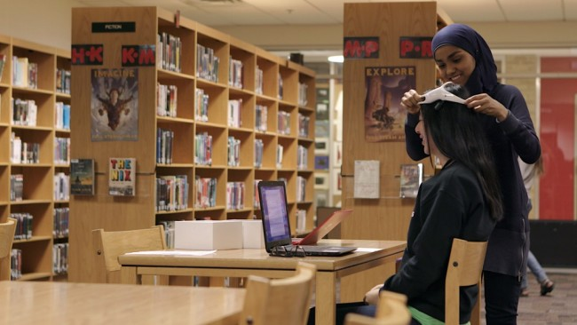 Kashfia in her natural environment, fitting brain sensors on a test subject in her school library. (Credit: Univision)