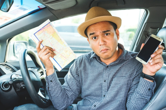 a man holding a map and a smartphone - getting lost navigation - shutterstock 643618435