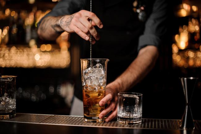 Bartender stirring cocktail - Shutterstock