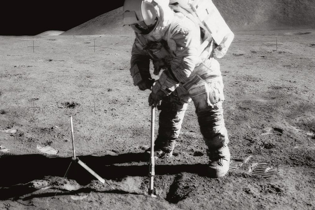 Astronaut James B. Irwin, lunar module pilot, uses a scoop in making a trench in the lunar soil during Apollo 15. (Credit: NASA)