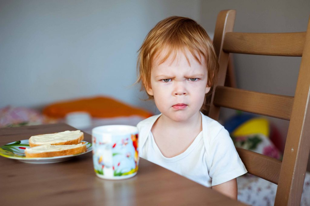 grumpy kid at table shutterstock