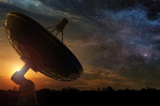 Radio Telescope with Rising Sun and Starry Sky - Shutterstock