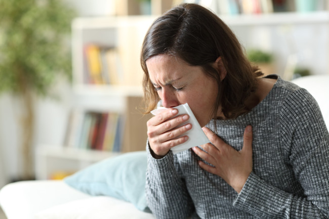 woman coughing at home into a tissue phlegm mucus illness - shutterstock