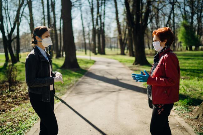 mask women chatting park - shutterstock