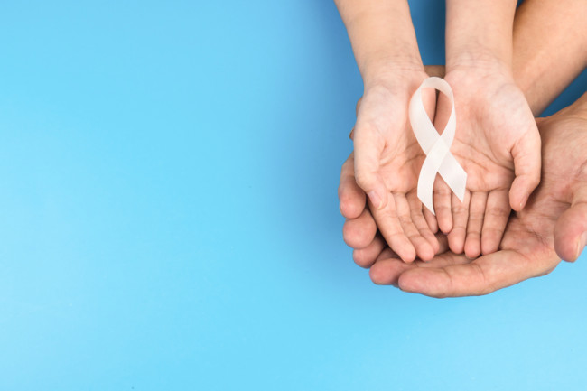 hands holding a white ribbon cancer awareness - shutterstock 1726701073
