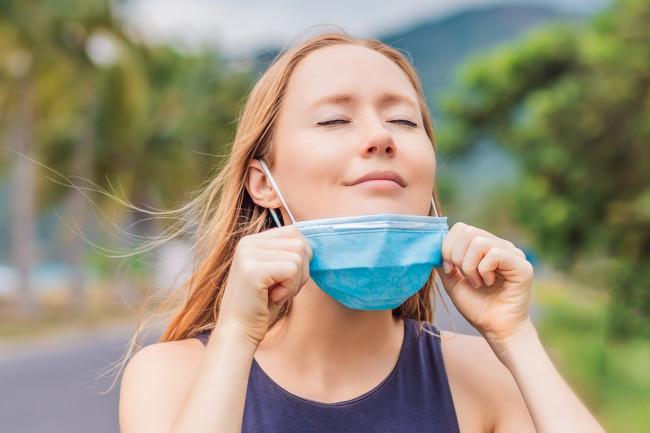 relief coronavirus deep breath woman take off mask - shutterstock