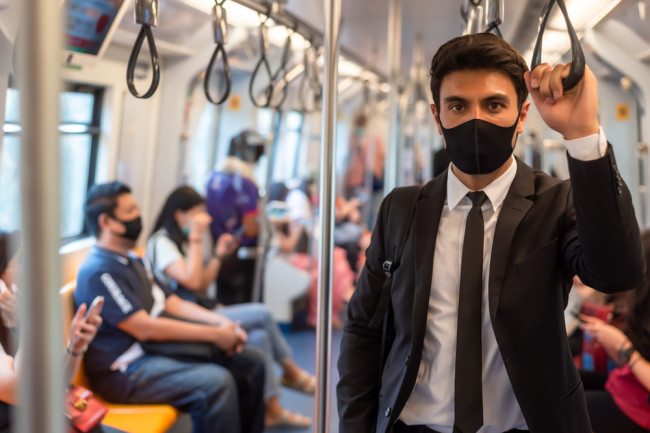 pandemic coronavirus masked man on a bus - shutterstock