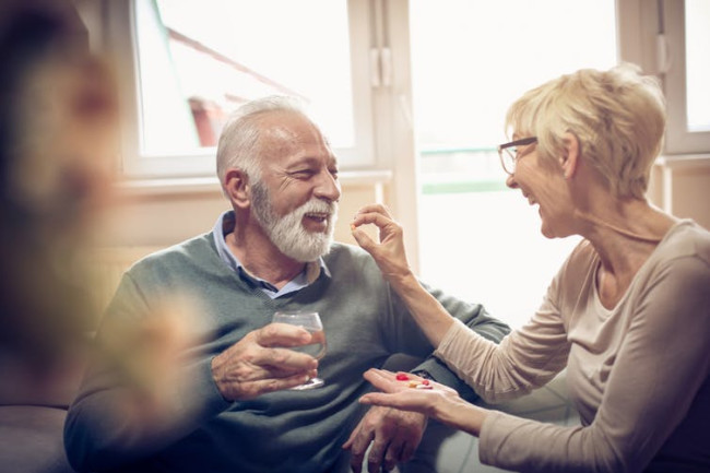 Old people taking medicine supplements pills - Shutterstock