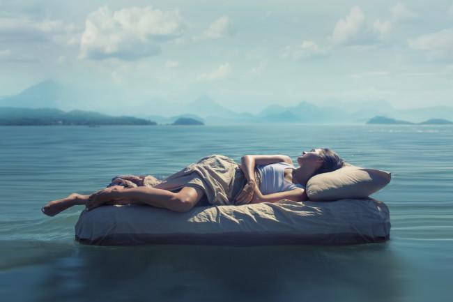 surreal dream bed in an ocean mountains dream interpretation - shutterstock