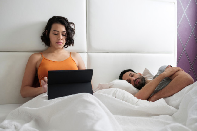 awake asleep couple bed laptop shutterstock