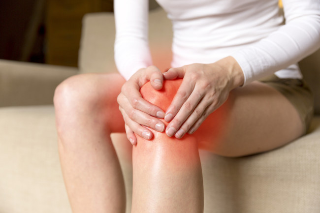 Woman holding her inflamed knee, inflammation - Shutterstock