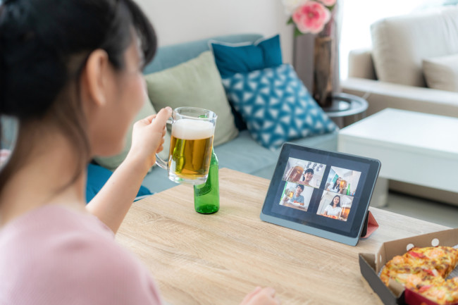 woman pandemic virtual happy hour drinking a beer - shutterstock