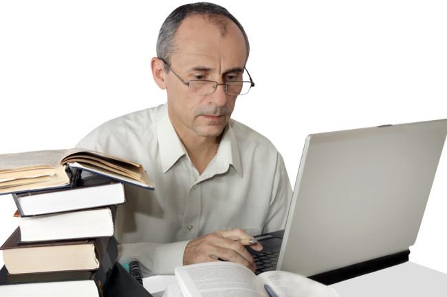Man Reading Books Computer Peer Review - Shutterstock