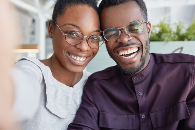 Smiling man and woman, both wearing glasses - Shutterstock