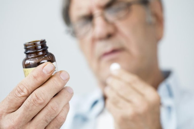 Reading label supplement pill medicine - Shutterstock
