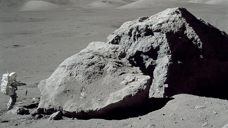 Apollo 17 astronaut Harrison H. Schmitt standing beside a boulder on the lunar surface. (Credit: NASA)