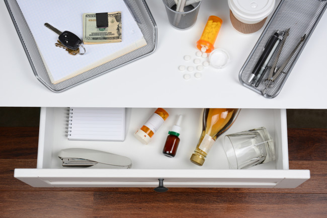 Desktop scene showing pills, coffee, and alcohol in a drawer - Shutterstock