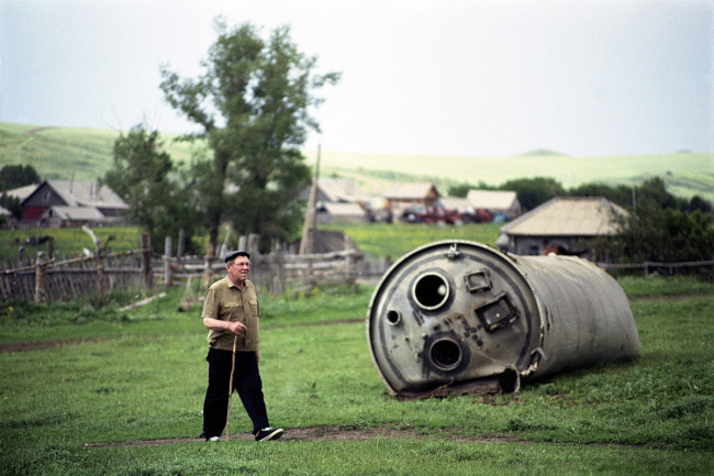 A farmer taking an evening stroll past the wreck of a Soyuz spacecraft. In this agricultural village, rockets routinely fall into people's back yards.
