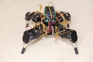A four-legged black robot with exposed wires.