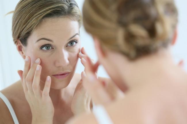 woman looking in mirror wrinkles - shutterstock