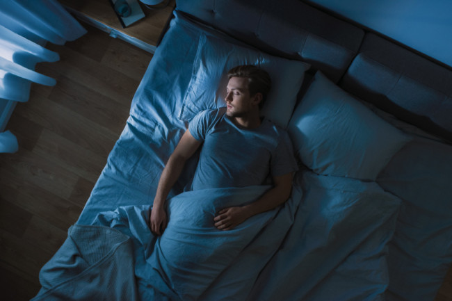 man sleeping in bed alone - shutterstock