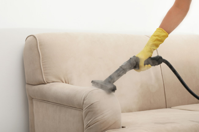 Arm with yellow rubber glove holds a hand-held steamer to a sofa - Shutterstock