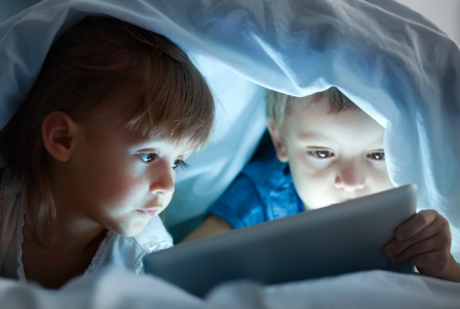 Kids on Phone Tablet Bed - Shutterstock