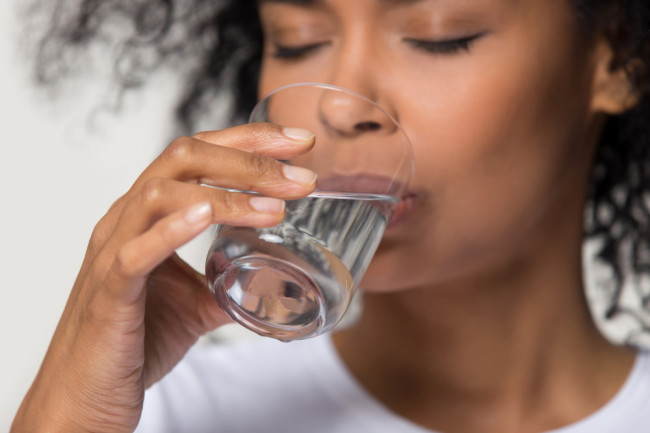 close up of woman drinking a glass of water - shutterstock 1391203490