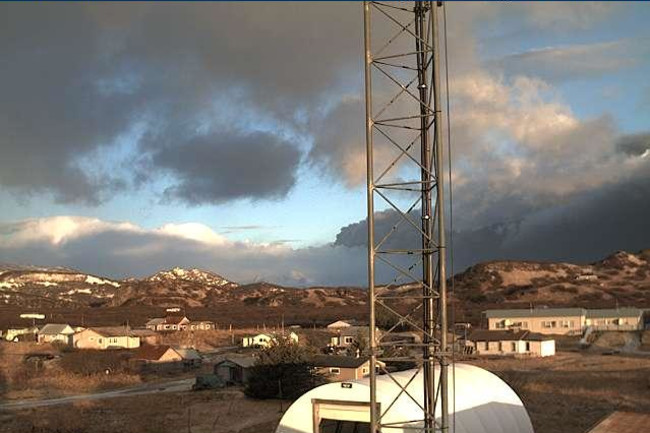 Image from the Perryville (Alaska) FAA webcam showing the plume from Veniaminof (dark cloud behind the antenna). FAA.