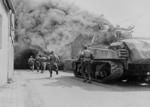 Soldiers of the 55th Armored Infantry Battalion and tank of the 22nd Tank Battalion, move through smoke filled street. Wernberg, Germany. Credit: Pvt. Joseph Scrippens, April 22, 1945 / Courtesy U.S. National Archives