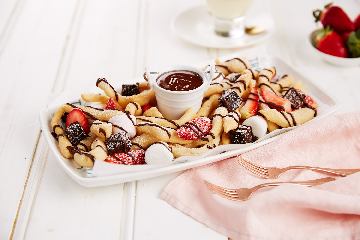 Strips of warm crispy fried dough, dusted in icing sugar, with strawberries, marshmallows and brownie pieces, served with rich chocolate sauce for dipping