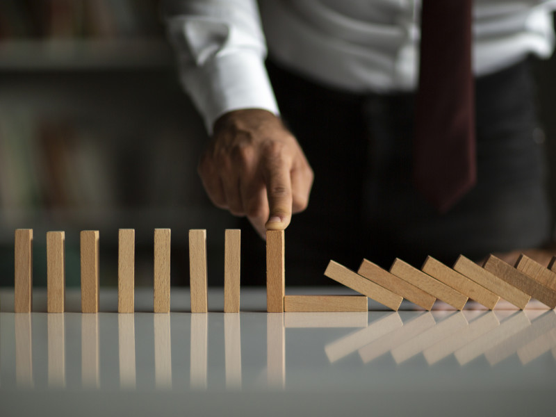Male business owner with finger on standing domino next to fallen dominoes