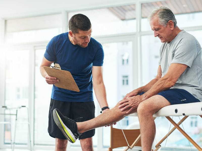 Male PT doing a consultation and assessment with a senior patient