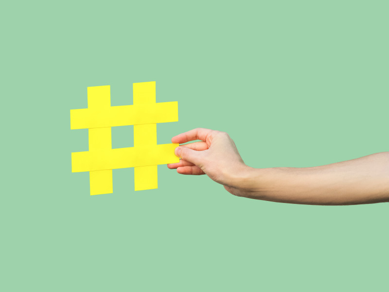 Close-up of hand holding large yellow hashtag sign