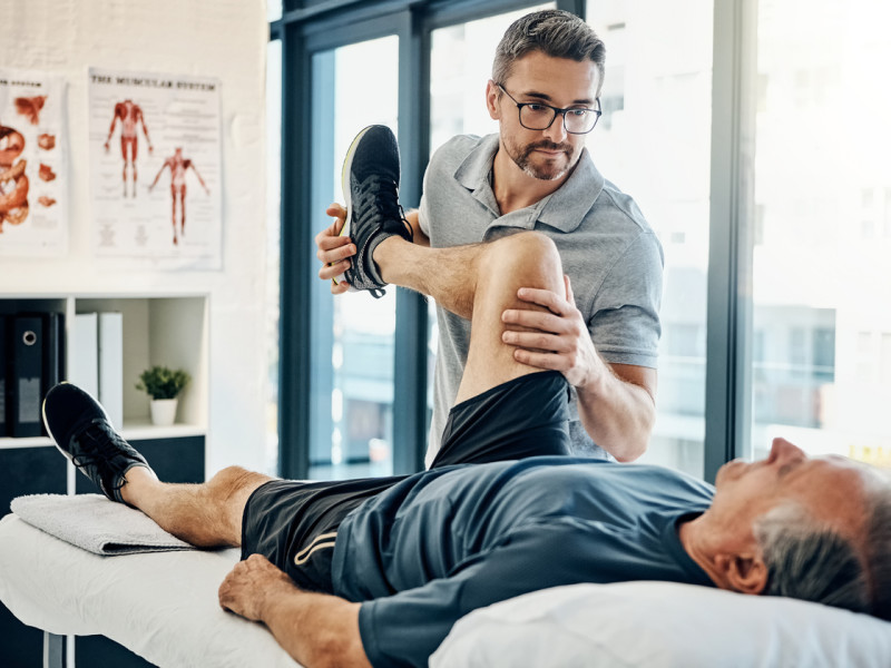 Male physical therapist with glasses stretching older patient on table.