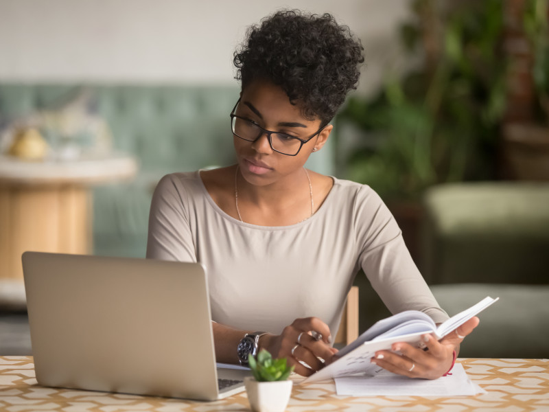 Young African American woman with glasses reading article on computer and taking notes
