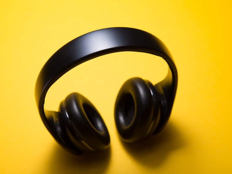 Black noise-cancelling headphones against bright yellow background
