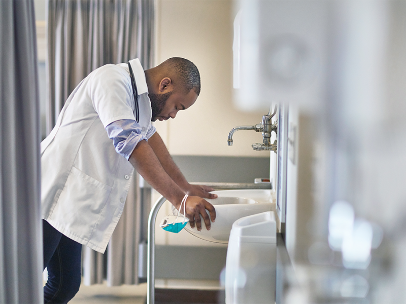 Stressed male nurse leaning over sink