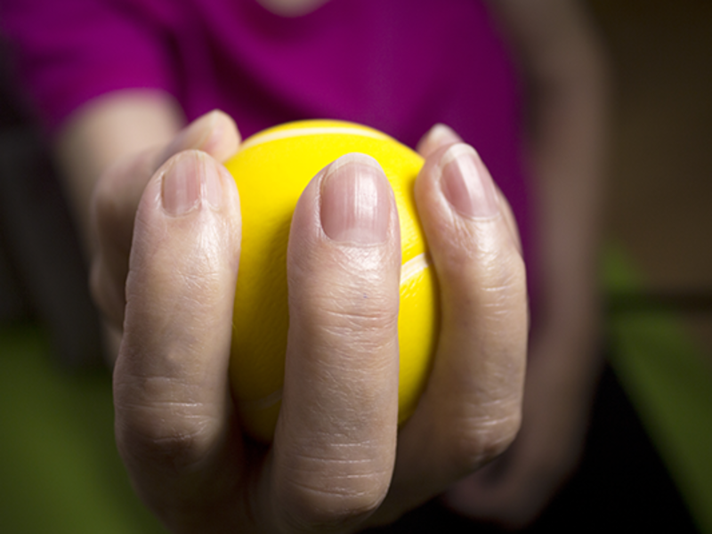 Close-up of woman's hand holding a yellow tennis ball
