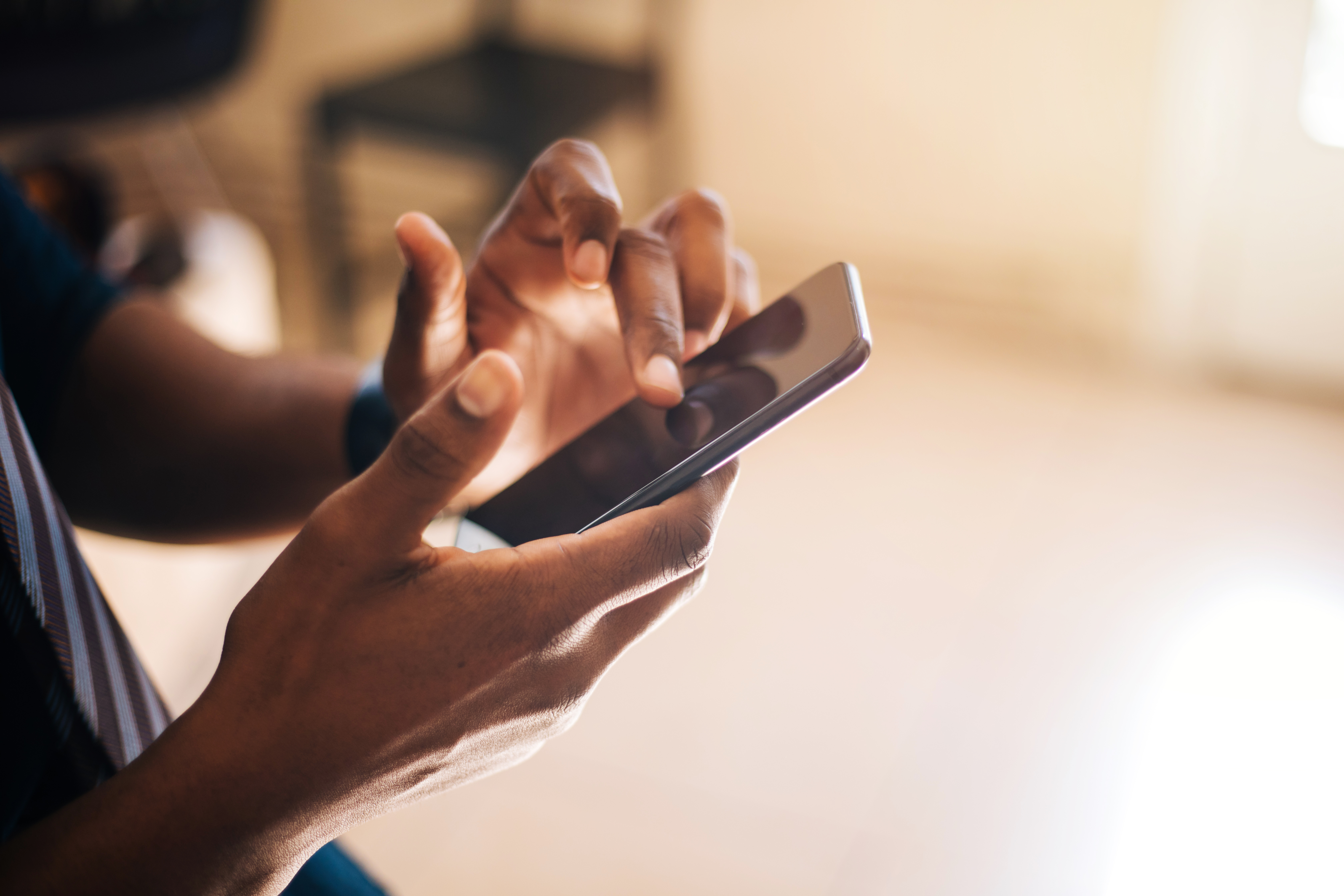 African American man scrolling through page on smartphone