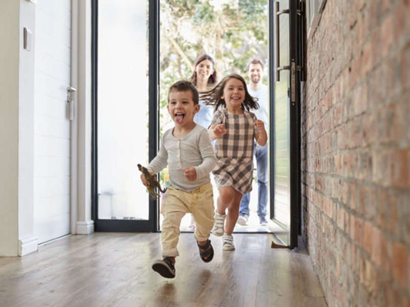 Children running into open house with parents behind them