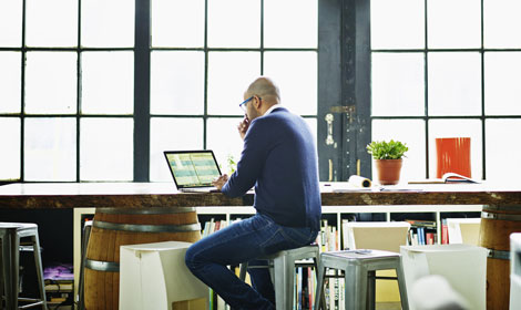 Man sitting at desk with laptop doing data analysis 470x280